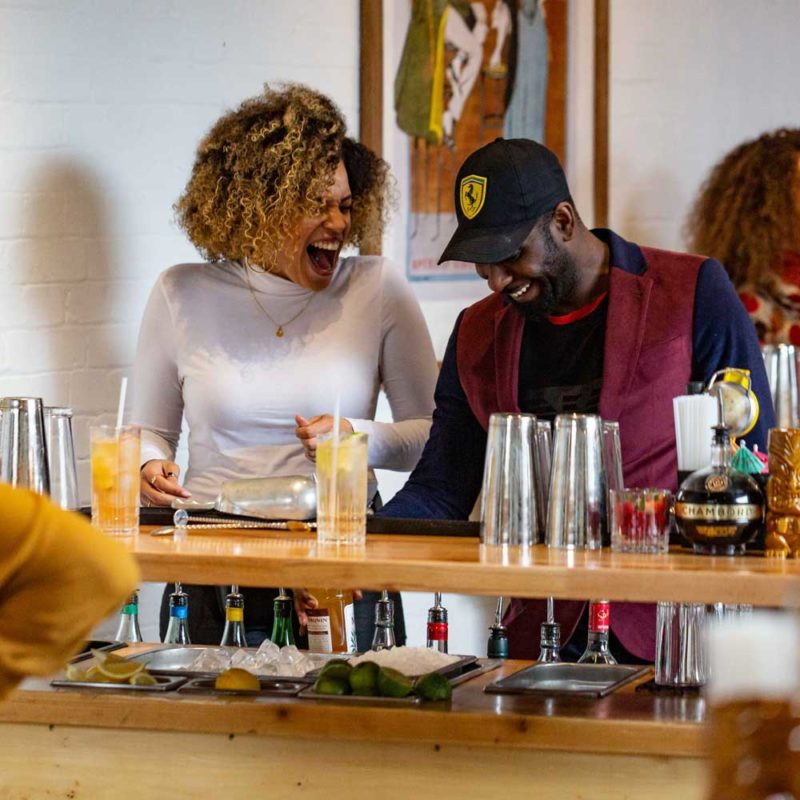 People laughing during their cocktail making class