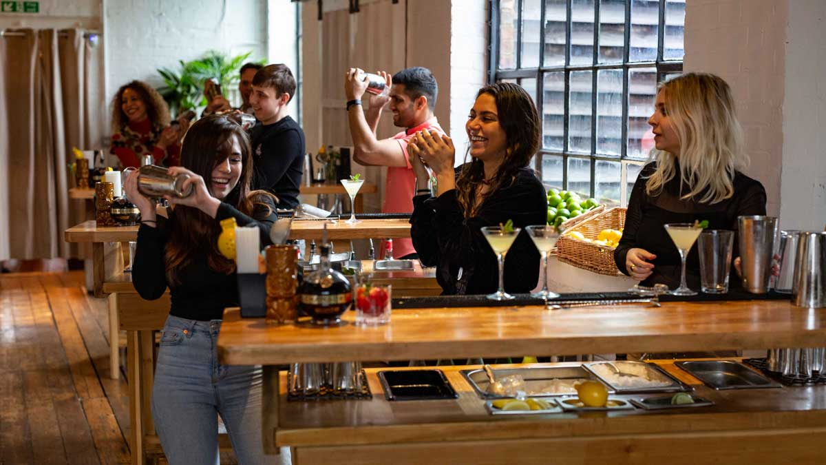Group of happy people in a cocktail making class in London