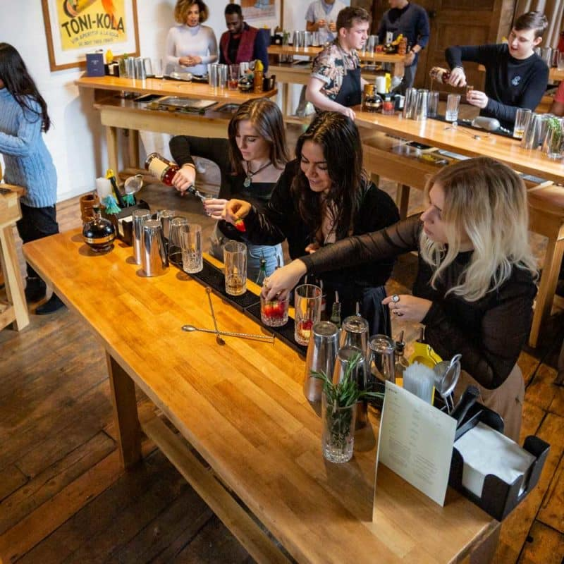 A group of people taking part in a Mixology Events cocktail making class for a company event