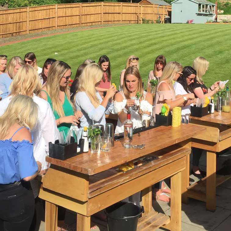 Group of women making cocktails on mobile bars set up in a back garden for a recent hen party