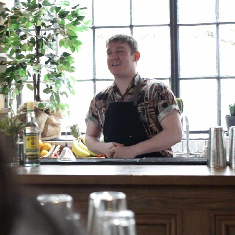 Male mixologist host at the front of a virtual cocktail making class