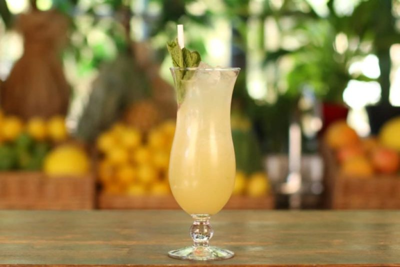 A Piña Colada, a classic tiki cocktail from Mixology Events virtual cocktail making classes, sits on a bar