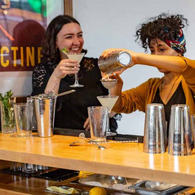 Two women enjoy a cocktail during a public Mixology Events cocktail making class in Shoreditch, east London