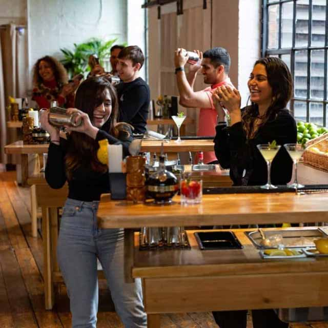 Two women take part in a public cocktail making class in Shoreditch, with others in background