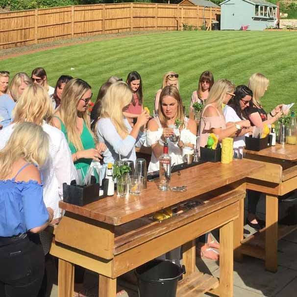 Group of women making cocktails on mobile bars set up in a back garden